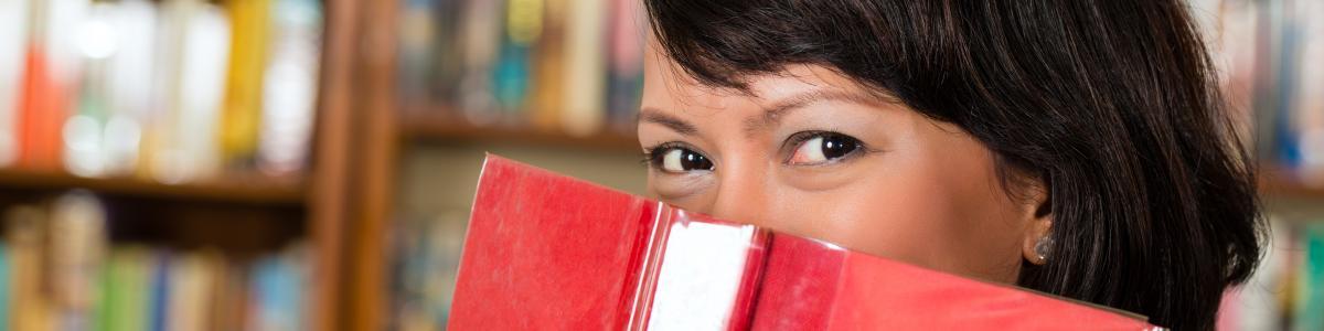 Kvinde der gemmer et smil bag en bog