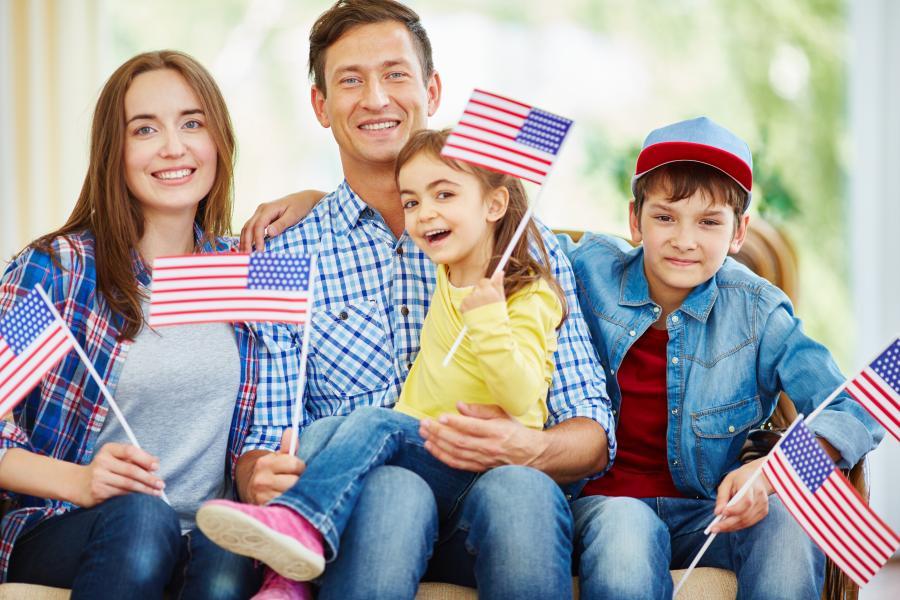 Mand og dame med to børn der holder Amerikanske flag