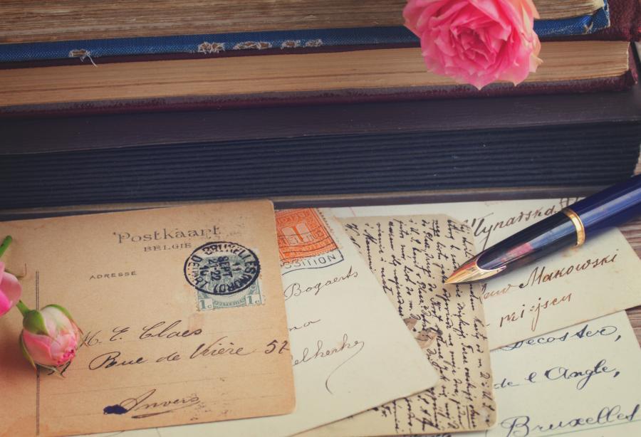 Breve og postkort samt fyldepen på et bord