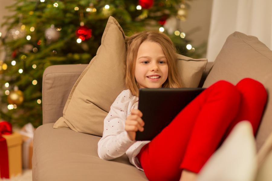 Pige læser foran juletræ