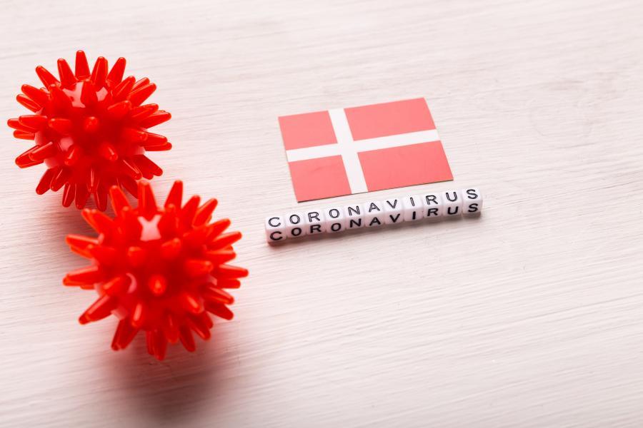 To røde kugler med pigge, et dansk flag samt terninger med bogstaver der staver ordet coronavirus