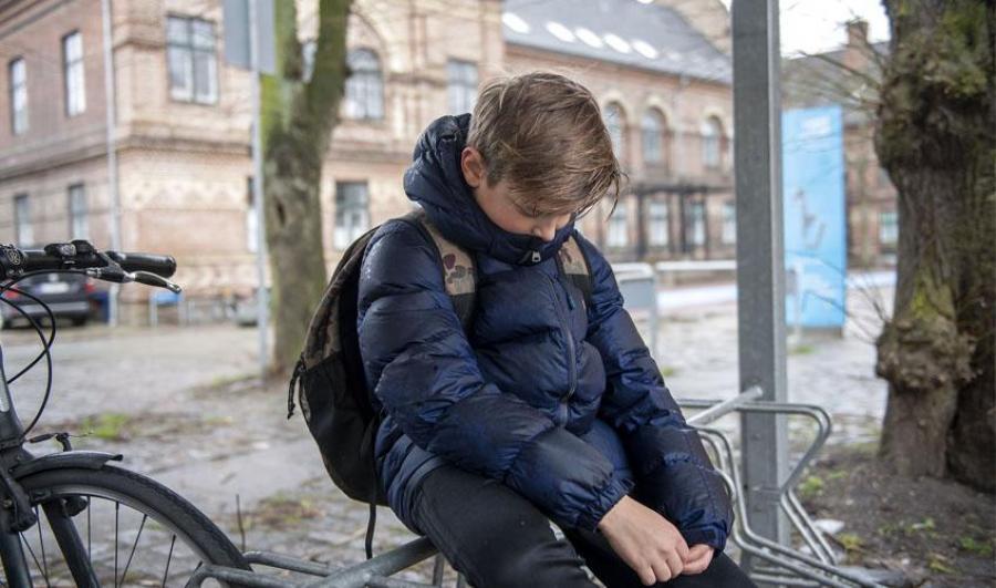 Dreng der sidder alene på cykelstativ